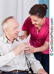 Disabled man drinking water in a hospice