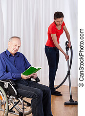 Nurse helping disabled with cleaning his house