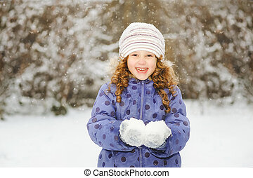 Winter portrait of a little smiling girl, holds in its hands...
