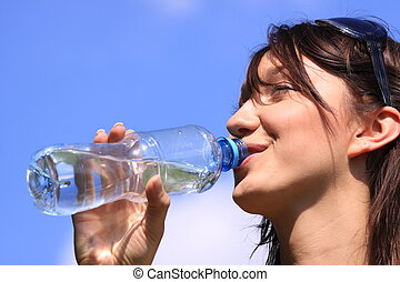 Girl drinking water against blue sky in sunny day