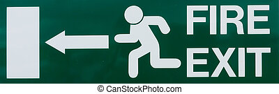 Fire Exit Sign - Green fire exit sign on a wood panel wall...