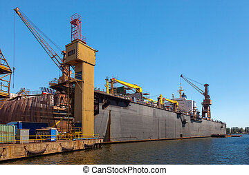 Dry dock  - Dry floating dock and cranes in shipyard.