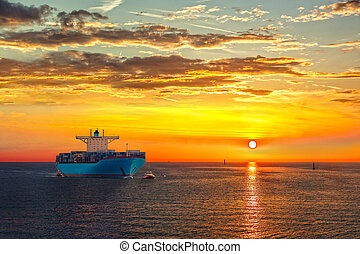 Container ship on sea road during sunrise