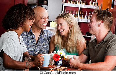 Friends in a Coffee House - Four adult friends meeting in a...