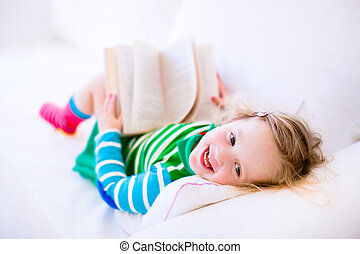 Litte girl reading - Happy laughing little girl reading a...