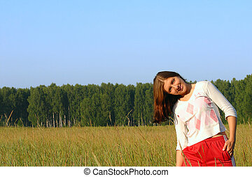 Happines girl in the field - The smiling girl standing in...
