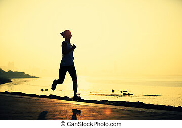 Runner athlete running at seaside woman fitness silhouette...