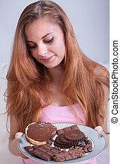 Girl holding a plate with chocolate snacks - Portrait of...