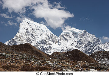 Snow mountains above grass hills, Himalaya - Cholatse and...