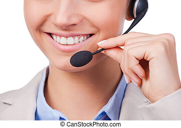 How may I help you? Close-up of young customer service representative adjusting her headset and smiling while standing against white background