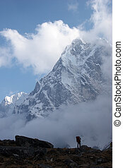 Climber looking at mountain covered with snow, Himalaya -...