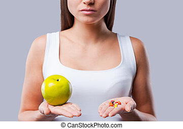 Make your choice!  Cropped picture of young woman holding an apple and pills in her hands
