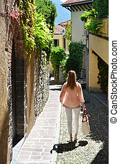 Girl on the cobbled street of Menaggio town Lake Como, Italy...