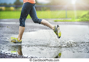 Girl of woman running in rainy weather - detail - Young...