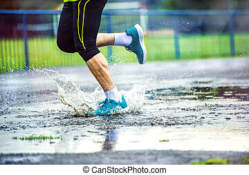 Detail of man running in rainy weather - Young man running...