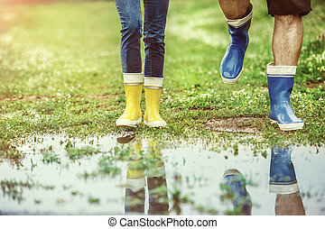 Details of young couple walking in muddy nature. - Young...