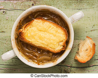 rustic french onion soup - close up of a bowl of rustic...