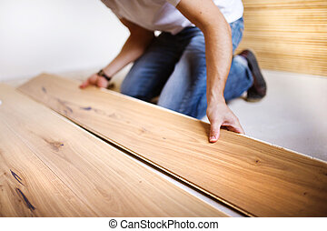 Handyman installing wooden floor - Unrecognizable handyman...