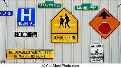 Traffic signs on a wall - Multiple traffic signs on a wall