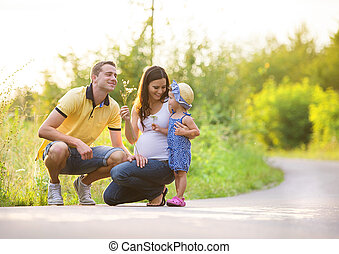 Family summer walk - Happy pregnant family with little...