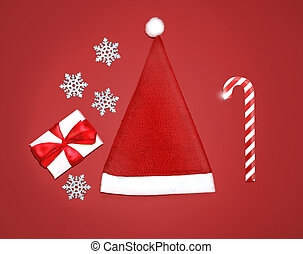 Christmas concept - santa cap, gift box, snowflakes and...