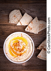 Hummus and pita bread - A bowl of fresh hummus, drizzled...
