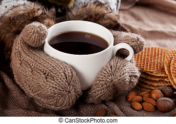 Cup of winter tea in hands in warm gloves