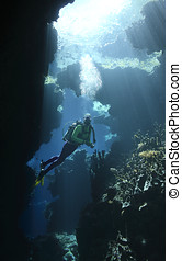 Scuba Diver in a cave with sunbeams - a female scuba diver...