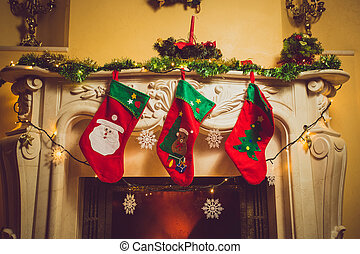 Toned photo of three red Christmas socks hanging on...