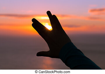 One hand making a Vulcan salute at golden hour sunset