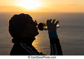 Woman quenching thirst with water at sunrsise