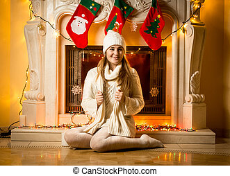 young woman in white sweater sitting at decorated fireplace
