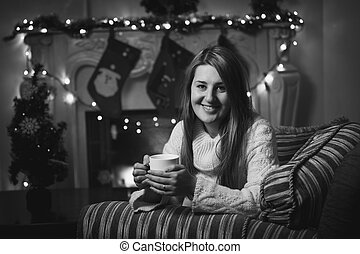 Monochrome portrait of smiling woman drinking tea at fireplace a
