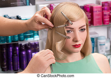 hairstylist makes hairstyle for beautiful girl
