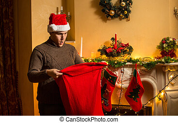 young man in red hat looking inside of Santa bag with...