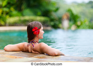 Girl in swimming pool - Beautiful woman relaxing in infinity...