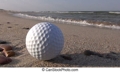 golf ball on sea resort beach sand - leisure concept