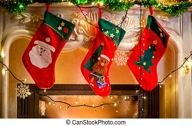 Three christmas stockings hanging on decorated fireplace -...