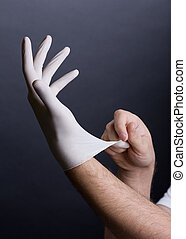 Putting on latex gloves - Male hands putting on latex gloves...