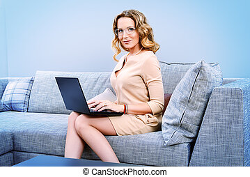 business lady - Beautiful business woman sitting on a couch...