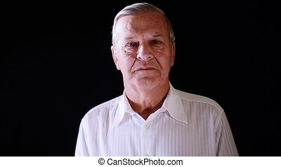 portrait of an elderly man - senior man on black background