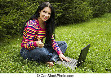 Woman  with laptop in nature give thumbs up
