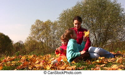 mother with children sit in autumn leaves