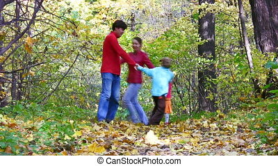 family of four round dance in autumn park - Family of four...