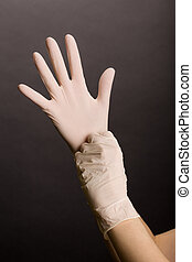 Putting on latex gloves - Female hands putting on latex...