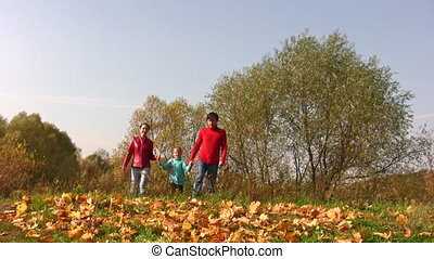 family with boy walking on autumn leaves