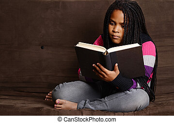 child reading book sitting on couch - portrait of a child...