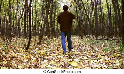 man throw leaves in autumnal wood - Man throw leaves in...