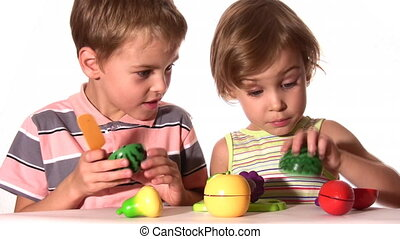 brother with sister with plastic fruits