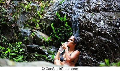 Young woman drinks water by waterfall on Koh Samui....